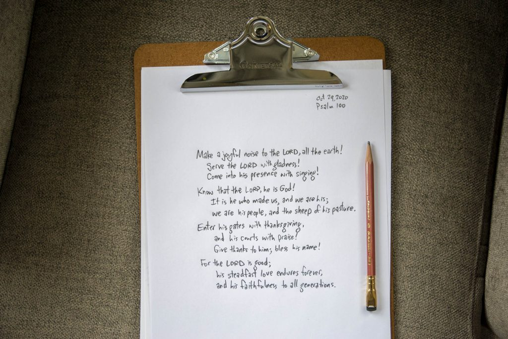 Psalm 100 hand-written with pencil on paper, with clipboard