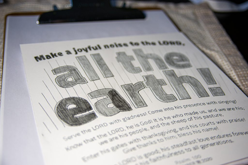 "Showing the process of darkening ""all the earth"" by shading over the text multiple times"